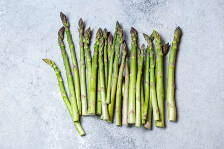 Fresh green asparagus on gray background top view copy space
