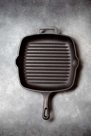 Black iron empty grill pan on gray concrette background. top view Imagens