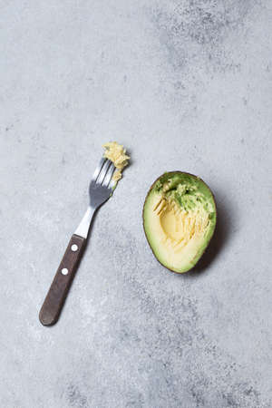 Half avocado on gray concrette background. Top view