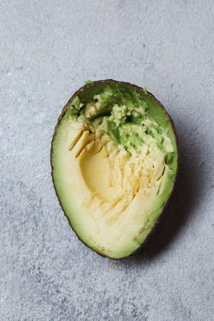 Half avocado on gray concrette background. Top view