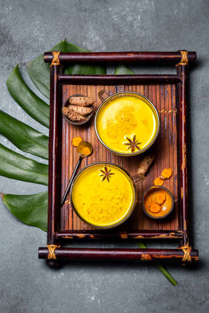 Hot drink golden milk turmeric latte with curcuma powder and spices. Top view