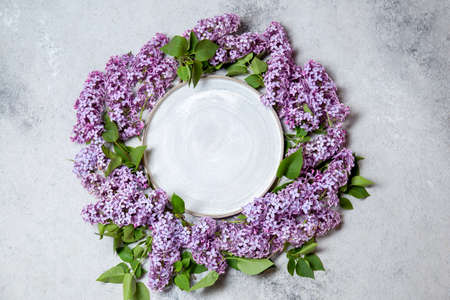 Spring background lilac around empty plate. Gray concrette background