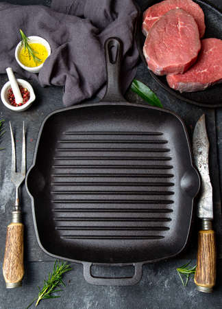 Cast Iron Grill pan, curving set, raw beef steaks and spices on black background. Top view Standard-Bild