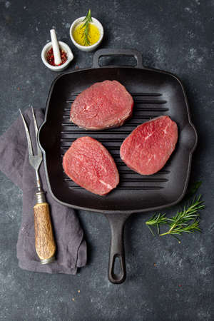 Raw beef steaks on cast iron grill pan. Top view, black background