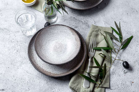 Mediterranean set table. Gray plates, forks, green napkins and olive tree branches