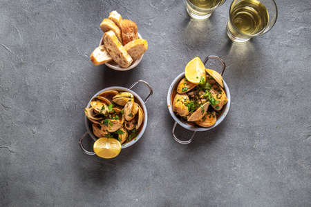 Clams with coriander, lemon and white wine in little pans on gray background, top view