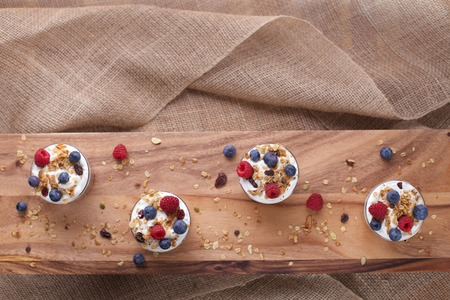sackcloth: Four Cups of Yogurt, Granola, Blueberries  and Raspberries on Wood and Burlap with Copy Space