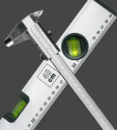 sliding scale: metallic sliding caliper and bubble level crossing Stock Photo