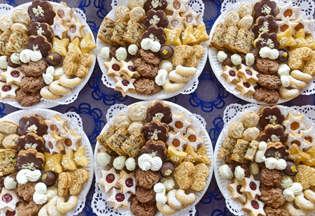paper plates: white paper plates with christmas biscuits on blue table cloth