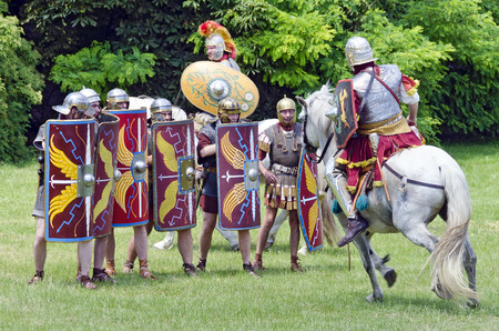 legionaries: mounted soldier of the group  Ala Prima Thracumvictrix attacking a gruop of legionaries, Roman festival 2014, Carnuntum, Austria Editorial