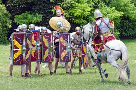 legionaries: mounted soldier of the group  Ala Prima Thracumvictrix attacking a gruop of legionaries, Roman festival 2014, Carnuntum, Austria Editorial
