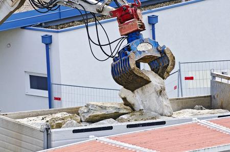gripper: gripper of a digger lifts a rock from a truck Stock Photo