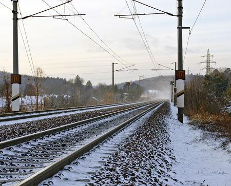 winterly: winterly snowy railway line with electrical overhead wiring Stock Photo