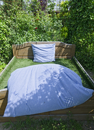 bedclothes: bed with blue and white bedclothes at a garden Stock Photo