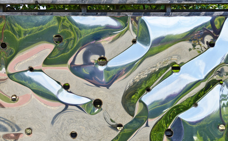 holed: mirroring on a wall  made of curved glossy sheet steel Stock Photo