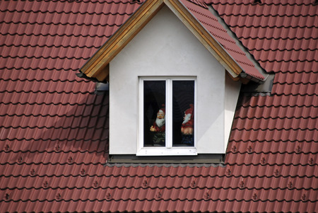 gnomos: techo de tejas rojas y buhardilla con gnomos de jardín de inmundicia Foto de archivo