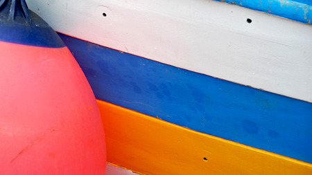 fender: boat hull white, blue and yellow colored with a round shaped red fender