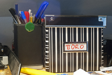 writing implements: office utensils and box with corresponding lid on a desktop