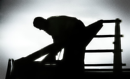 timbering: silhouette of a roofer on an uncovered roof truss Stock Photo