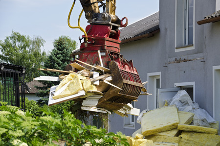 house demolition: removing of insulation material and a digger at the demolition of a residential house