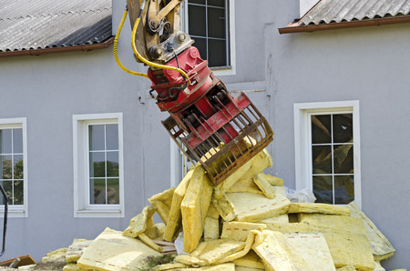 grapple: removing of insulation material and a digger at the demolition of a residential house