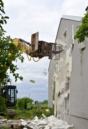 grapple: Removing a Wrmeschutzfassade with an excavator during the demolition of a residential building; removing of Thermal insulation from the fronf of a residential house by a digger at the demolition