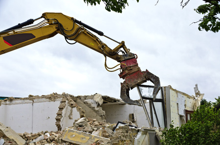 grapple: Entfernen eines Fensters durch einen Bagger beim Abbruch eines Wohnhauses; removing of a window by a digger at the demolition of a residential house Stock Photo