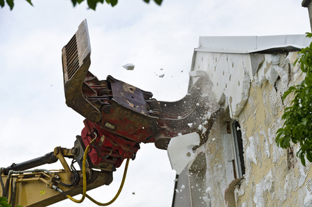 demolishing: Removing a Wrmeschutzfassade with an excavator during the demolition of a residential building; removing of Thermal insulation from the fronf of a residential house by a digger at the demolition