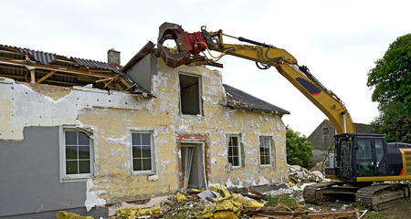 grapple: Abbruch eines Wohnhauses durch einen Bagger mit Greifer; demolition of a residential house by a digger with a picker arm