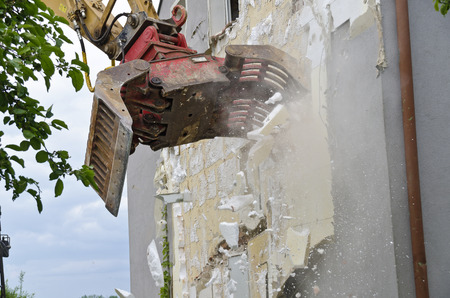 grapple: removing of Thermal insulation from the fronf of a residential house by a digger at the demolition