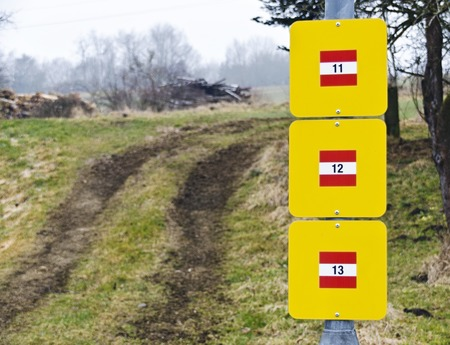 12 13: tractor track and pole with yellow signpost with number 11, 12 and 13 on red-white-red background