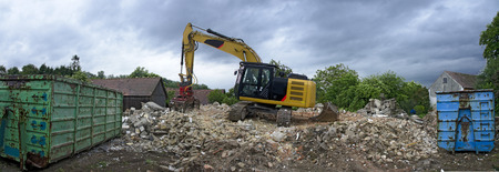 a digger with a picker arm on a mountain of rubble from the demolition of a residential house and two skips