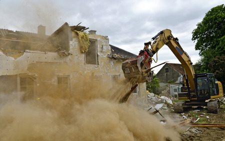 Demolition of a residential house by a digger with a picker arm Caused a big dust cloud Standard-Bild