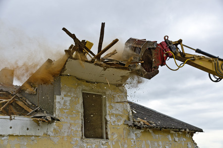 grapple: Demolition of a residential house by a digger with a picker arm
