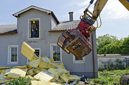 rockwool: removing of insulation material and a digger at the demolition of a residential house