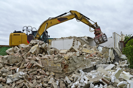 Demolition of a residential house by a digger with a picker arm on a mountain of rubble