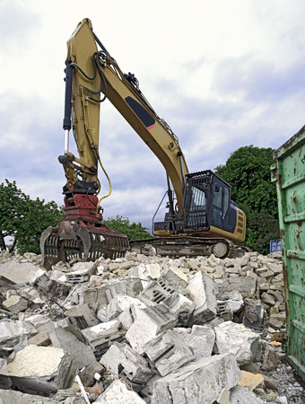 grapple: a digger with a picker arm on a mountain of rubble from the demolition of a residential house