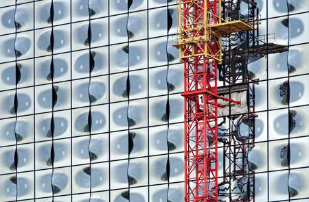 crane parts: Parte de la fachada de la Filarm�nica del Elba Concerthall en Hamburgo y partes de una gr�a de construcci�n de color rojo y amarillo, Alemania, 2012