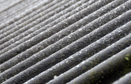 cladding tile: old weather-beaten roof cladding made from waved asbestos-cement sheets