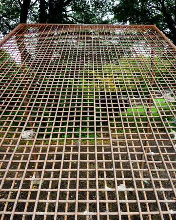 reinforcing: coarse soil sieve made from reinforcing steel standing betwen trees Stock Photo