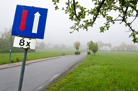 give the way: road with traffic sign give way to oncoming traffic for eight times Stock Photo