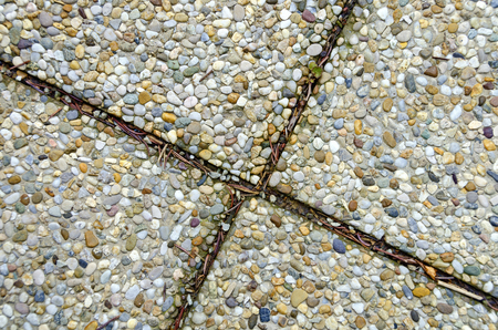 gaps: sidewalk-flags of exposed-aggregate concrete with dirty gaps Stock Photo