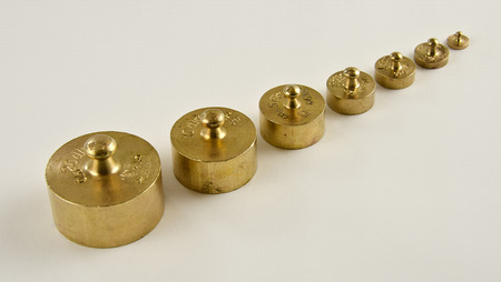 calibrated: set of weights made from brass with hallmarks in a row