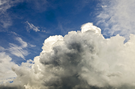 billowing: rising up billowing clouds of a thunder storm at a blue sky