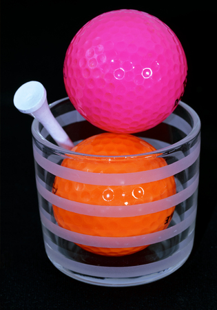 orange and purple golf balls with white tee in a drinking glass on dark background Stock Photo