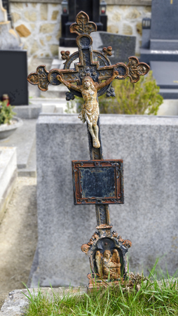 empty tomb: old rusty iron grave cross at a cemetery Stock Photo