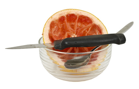 bisected: remains of a red grapefruit with bowl, knife and spoon