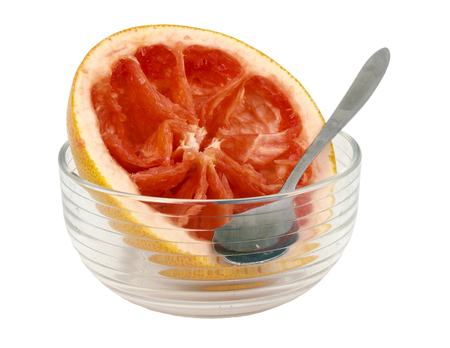 bisected: remains of a red grapefruit with bowl and spoon Stock Photo