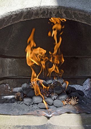 briquettes: burning charcoal briquettes and pine cones with blazing flames in the combustion chamber of a concreted barbecue