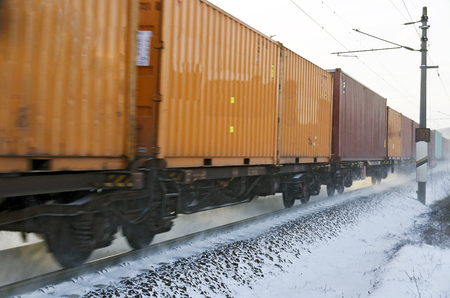 winterly: cargo rail with container wagons running on winterly snowy track Stock Photo